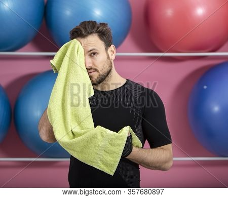 Portrait Of A Fit Tired Man Wiping His Face With A Towel In The Gym During Training
