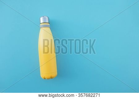Reusable Eco-friendly Stainless Steel Yellow Bottle On Light Blue Background.