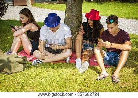 Group Of Young People Sitting Under Tree, Using Their Smartphones And Communicating With Each Other