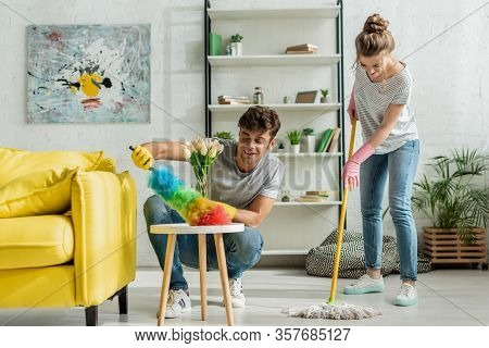 Happy Man And Woman Doing Spring Cleaning In Apartment