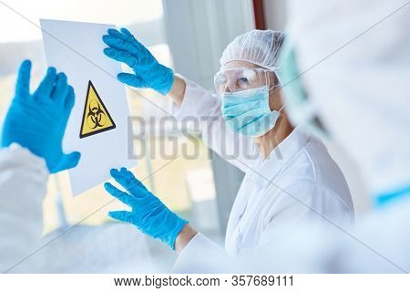 Biohazard warning sign in clinic is attached by clinic staff in protective clothing during coronavirus epidemic