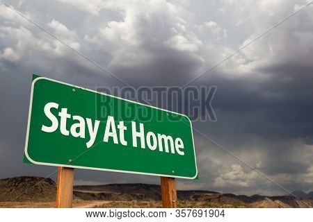 Stay At Home Green Road Sign Against An Ominous Cloudy Sky.