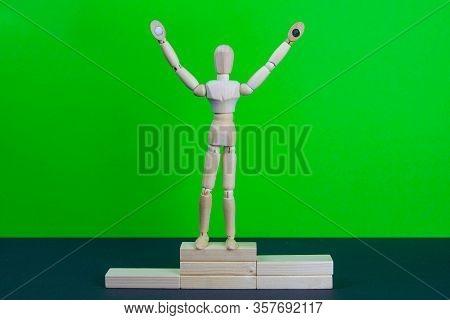 Full Length Portrait Of Male Winner On Winners Pedestal, On Green Background. The Composition Of 3 C