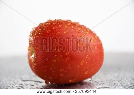 Fresh Tomato With Dripping Water. Ripe Natural Tomatoe Close-up. Organic Tomato On White Background