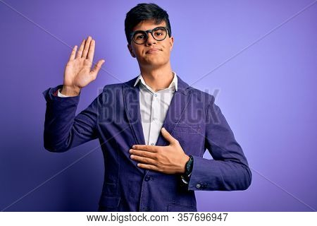 Young handsome business man wearing jacket and glasses over isolated purple background Swearing with hand on chest and open palm, making a loyalty promise oath