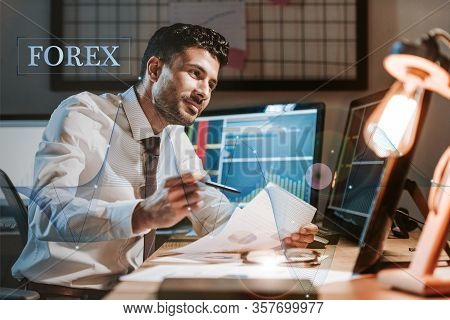 Happy Bi-racial Trader Holding Paper Near Computer With Graphs And Forex Letters