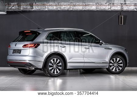 New Silver Volkswagen Touareg- Back View On Dark Background.   Modern Crossover Made In Germany . No