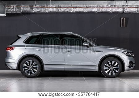 New Silver Volkswagen Touareg- Side View On Dark Background.   Modern Crossover Made In Germany . No