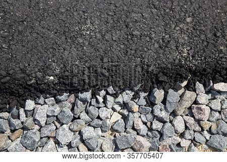 Small Rubble And A Layer Of Asphalt At The Construction Site Of A New Highway Or Roadway, Closeup