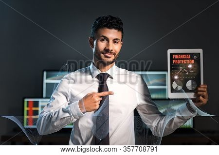 Happy Bi-racial Trader Pointing With Finger At Digital Tablet With Financial Protection Letters On S