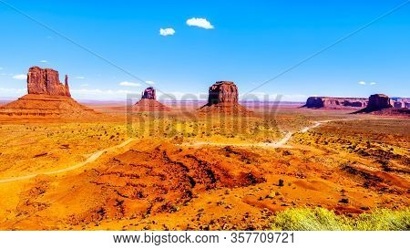 The Gravel Road Winding Around Mitten Buttes, Merrick Butte And Other Large Sandstone Formations In