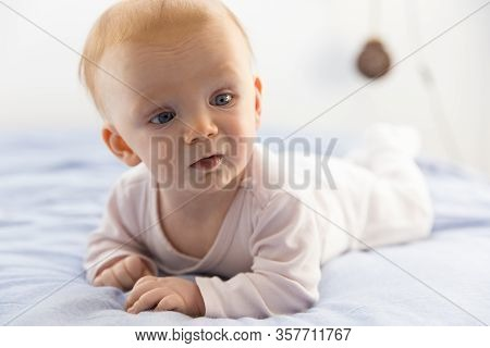Adorable Red-haired Baby Lying On Tummy And Looking Aside. Close-up Portrait Of Newborn Child With B
