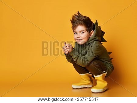 Active And Frolic Kid Boy In Hoodie With Dinosaurus Spikes At His Back And Cowl And In Yellow Rubber