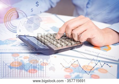 Researcher Using Calculator With Financial Analysis Graphs. Businessman Working With Papers At Desk.