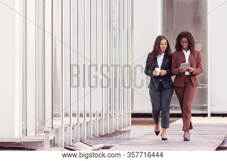 Full Length Portrait Of Smiling Businesswomen Walking With Tablet. Cheerful Young Women Wearing Form