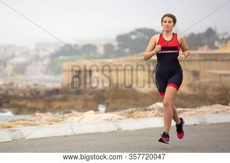 Young Female Jogger During Workout. Full Length View Of Sporty Young Woman In Sportswear Running On