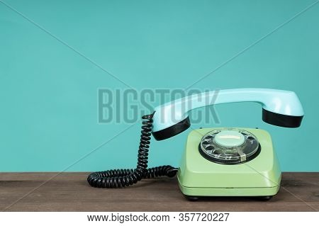 Old Telephone On Wooden Table In Front Of Green Background. Vintage Phone With Taken Off Receiver. V