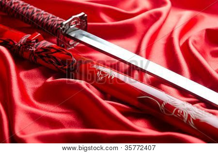 Japanese sword takana on red satin background