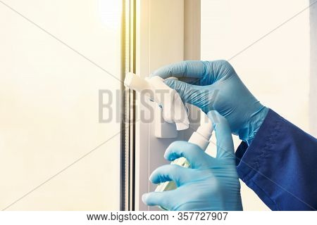 Doctor In Rubber Gloves Disinfects Window Handles With Sanitizer And Napkins. Convalescence