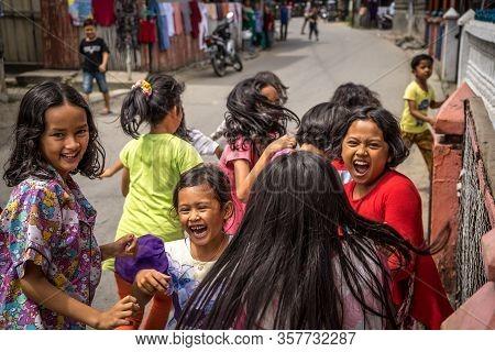 Panyambungan, Indonesia - June 21, 2018: Children Excited And Afraid Of Camera Running Away On The S