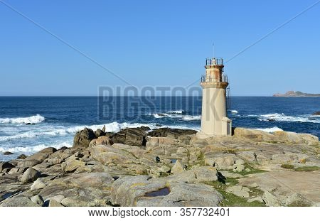 Famous Muxia Old Lighthouse Located At Camino De Santiago European Religious Pilgrimage With Blue Sk