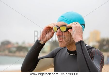 Man In Wetsuit Wearing Goggles. Close-up View Of Male Swimmer Wearing Sportswear And Protective Glas