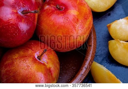 Close-up Yellow And Orange Plums (variety Known As Honey Or Mirabelle). In Clay Bowl And Space To In