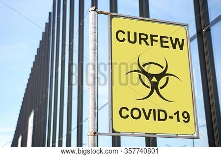 Street Sign With Curfew Inscription With A Virus Covid-19 Icon On The Background Of A Fashionable Bu