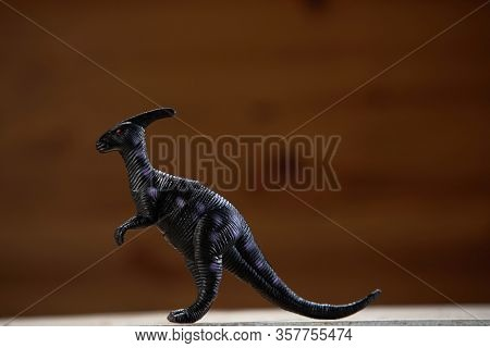 side view of the toy dinosaur with wooden background