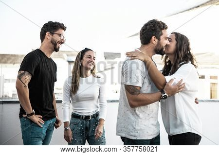Happy Cheerful Old Friends Greeting And Kissing Each Other On Apartment Terrace. Young Men And Women
