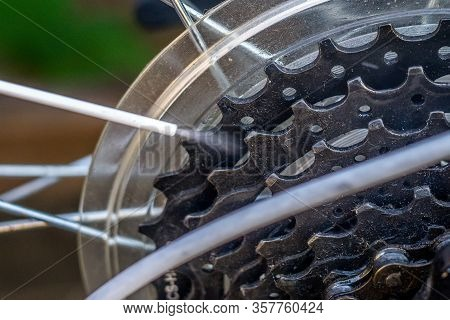 Cleaning And Greasing The Bicycle Chain And Transmission With An Oil Spray. Close-up, Selective Focu