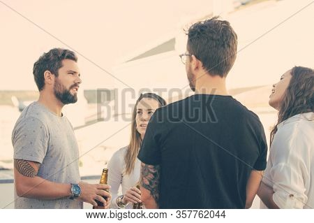 Group Of Friends Sharing News Over Bottle Of Beer On Outdoor Terrace. Young Men And Women In Casual