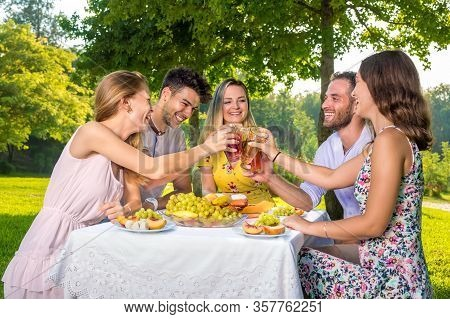 Happy Young Group Of Five Teenage Friends Enjoying Picnic Party In Park.