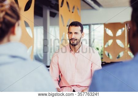 Friendly Confident Business Coach Speaking Before Audience. Young Business Man In Casual Holding Not