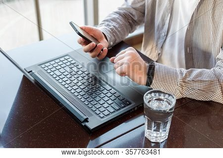 Remote Work. Man Using Laptop, Holding Smart Phone For Business Work Or Study, Smart Watch. Freelanc