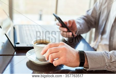 Man In Smart Watch Drinking Coffee On Work Space. Man Using Laptop, Holding Smart Phone For Business