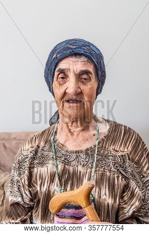 Portrait Of An Elderly Turkish Woman With Traditional Bonnet Holding A Walking Stick While Sitting I