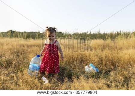 Little Girl Collects Trash Scattered In The Forest. Little Girl Collects Trash Scattered In The Fore