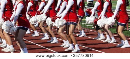 High School Cheerleaders In Red And White Unifors Perforiming For The Crowd During Homecoming Footba