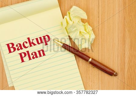 Backup Plan Message On A Yellow Legal Notepad Paper With Crumpled Paper And Pen On Wood Desk