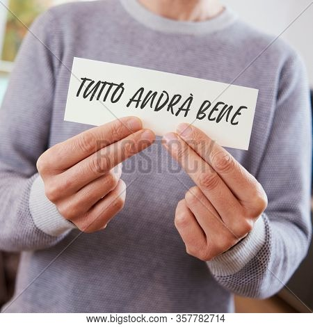 man, in casual wear, showing the message tutto andra bene, everything is going to be alright written in italian, in a piece of paper, a popular message of hope in italy during the covid-19 pandemic