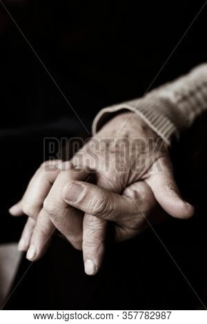 closeup of a young caucasian man holding the hand of a senior caucasian woman, with their fingers entwined with affection, in sepia toning
