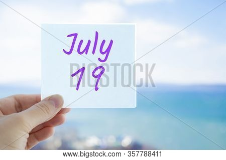 July 19th. Hand Holding Sticker With Text July 19 On The Blurred Background Of The Sea And Sky. Copy