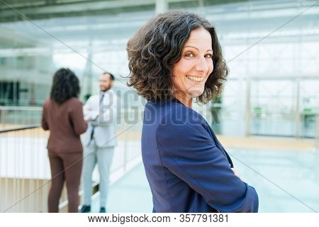 Happy Successful Business Woman Posing With Arms Folded, Looking At Camera, Smiling. Her Male And Fe