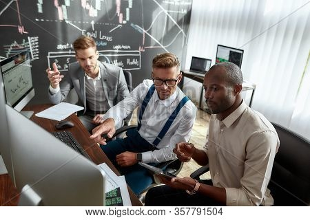High Angle View Of Three Colleagues Traders Sitting By Desks In Front Of Computer Monitors And Discu