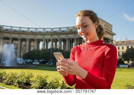 Young Beautiful Smiling Woman Wanderer Using Navigator Program On Mobile Phone During Her Walking In