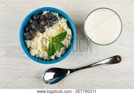 Cooked Dairy Rice Porridge With Blueberry And Spearmint In Blue Bowl, Glass Of Milk, Spoon On Light