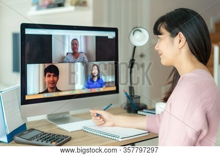 Back View Of Asian Business Woman Talking To Her Colleagues About Plan In Video Conference. Multieth
