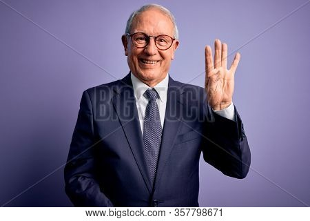 Grey haired senior business man wearing glasses and elegant suit and tie over purple background showing and pointing up with fingers number four while smiling confident and happy.