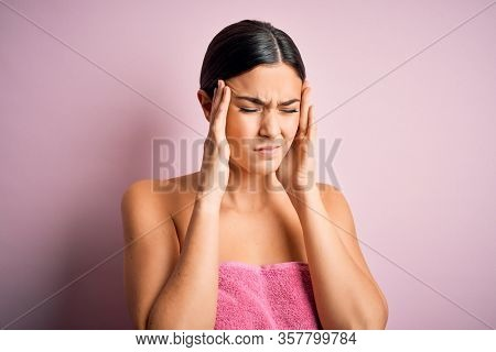 Young beautiful girl wearing towel shower after bath standing over isolated pink background suffering from headache desperate and stressed because pain and migraine. Hands on head.